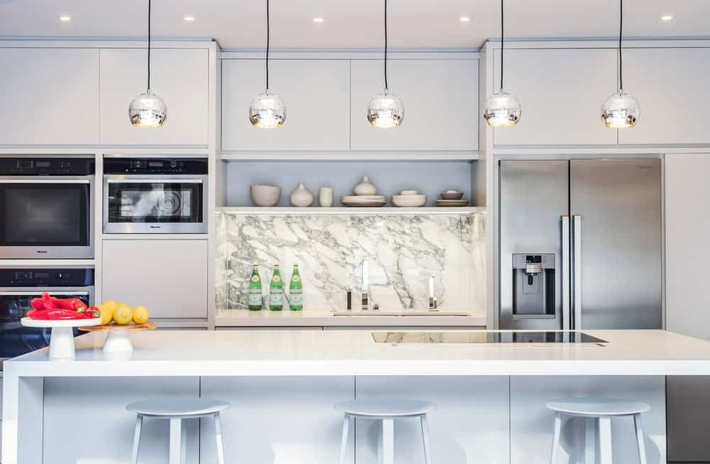 A focused look at this kitchen's white center island with a breakfast bar lighted by lined up pendant lights.