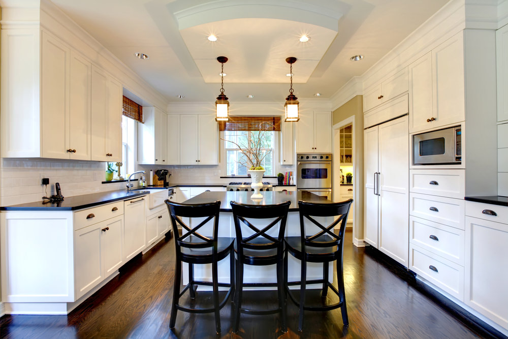 This kitchen features black countertops on both kitchen counters and center island with a breakfast bar lighted by pendant and recessed lights set on the area's tray ceiling.