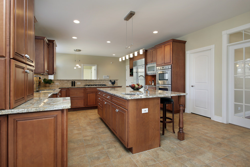 This kitchen features brown cabinetry and kitchen counters, along with a brown center island with a breakfast bar. The kitchen also has marble countertops.
