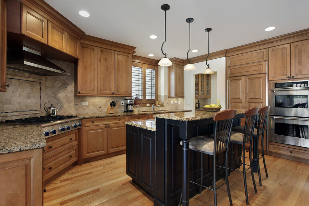 This kitchen has brown cabinetry and kitchen counters, along with granite countertops. It also offers an island with a separate breakfast bar counter.