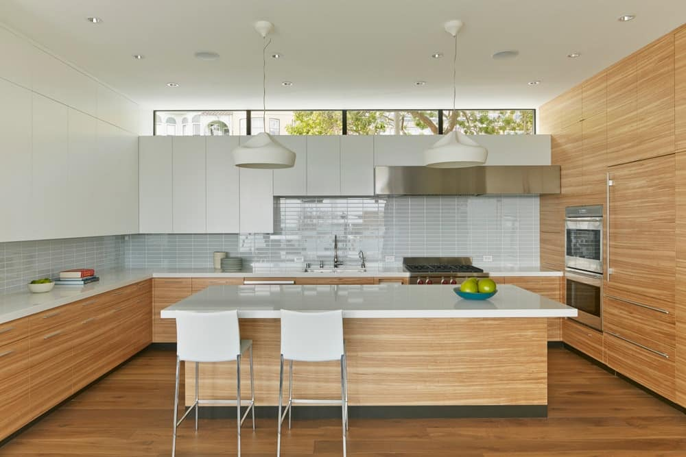 Modern kitchen with brown kitchen counters and a brown center island, both have white countertops. This kitchen also has a breakfast bar lighted by a pair of pendant lights.