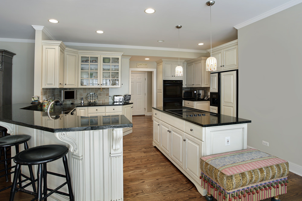 A kitchen with black countertops on both kitchen counters and center island. There's a breakfast bar counter as well.