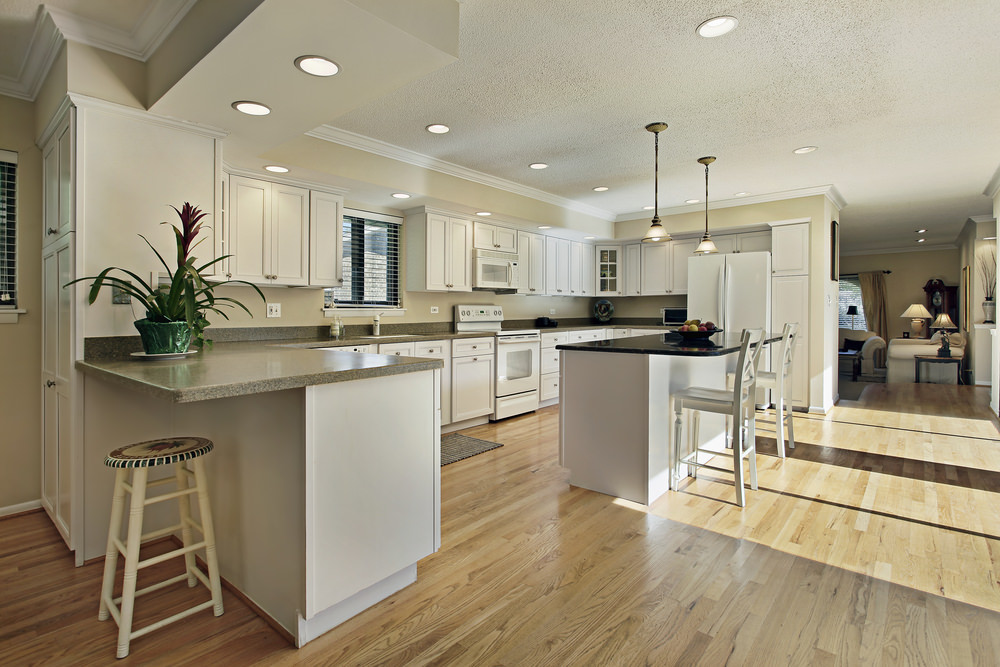 A spacious kitchen area with a breakfast bar counter lighted by pendant lights. The area features hardwood floors and a ceiling lighted by recessed and pendant lights.