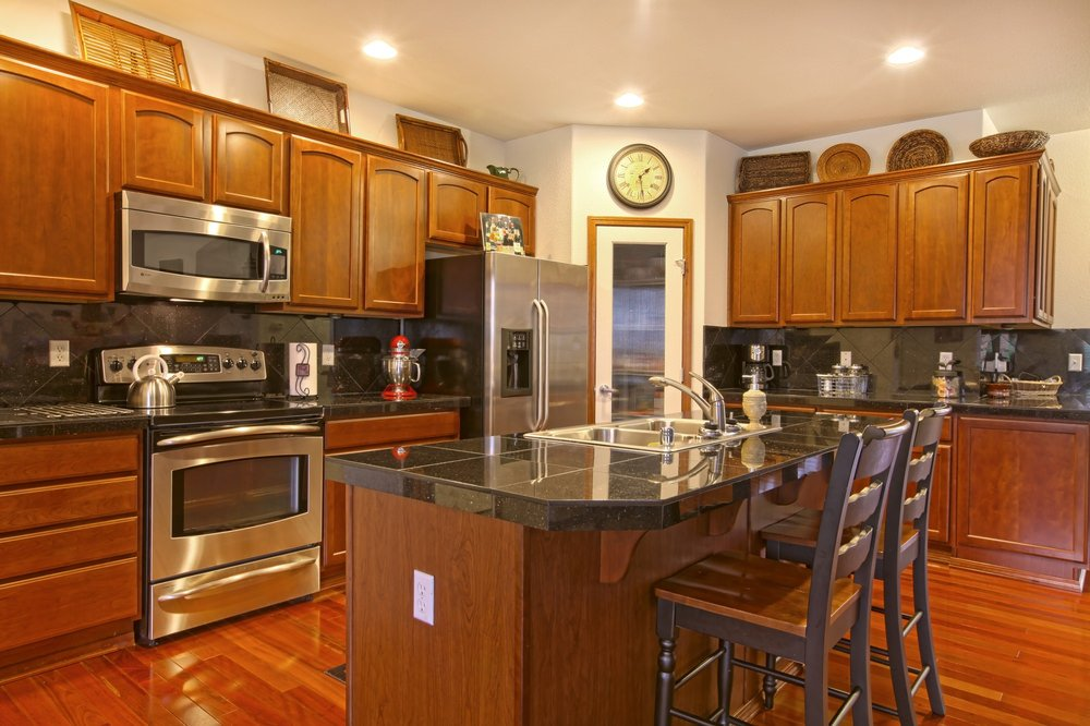 A focused look at this kitchen's island featuring a black tiles countertop similar to the kitchen counters. It also offers space for a breakfast bar.