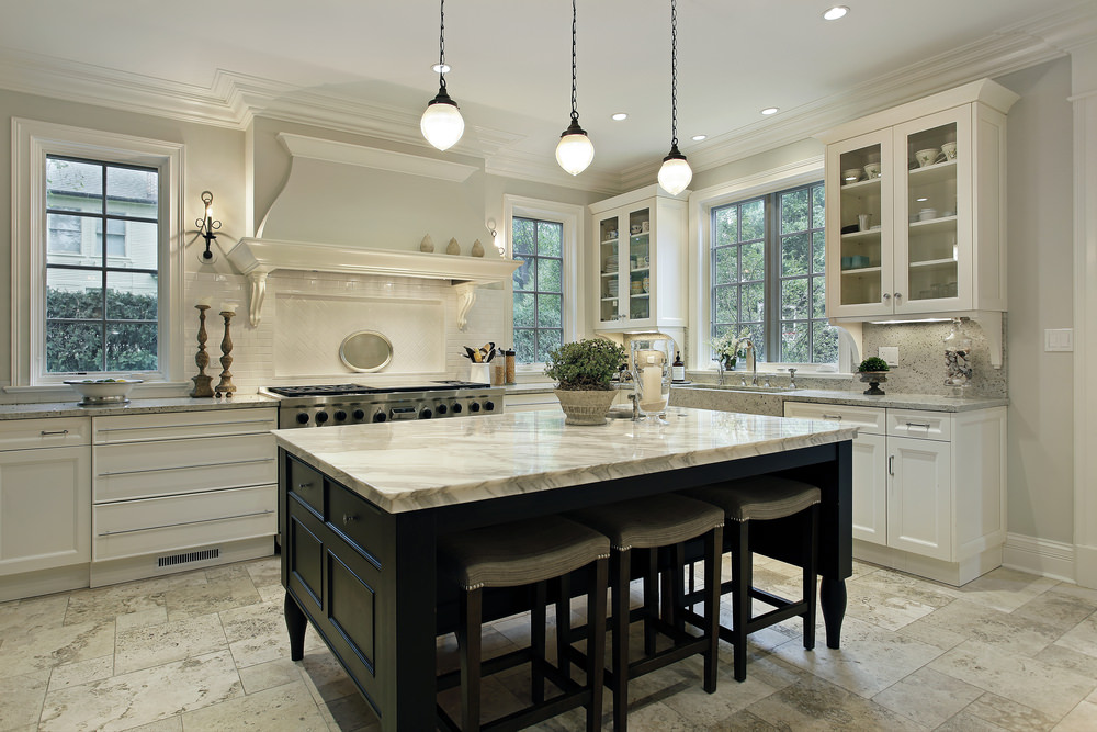 A close up look at this spacious kitchen's center island with a thick marble countertop and has a breakfast bar lighted by pendant lights.