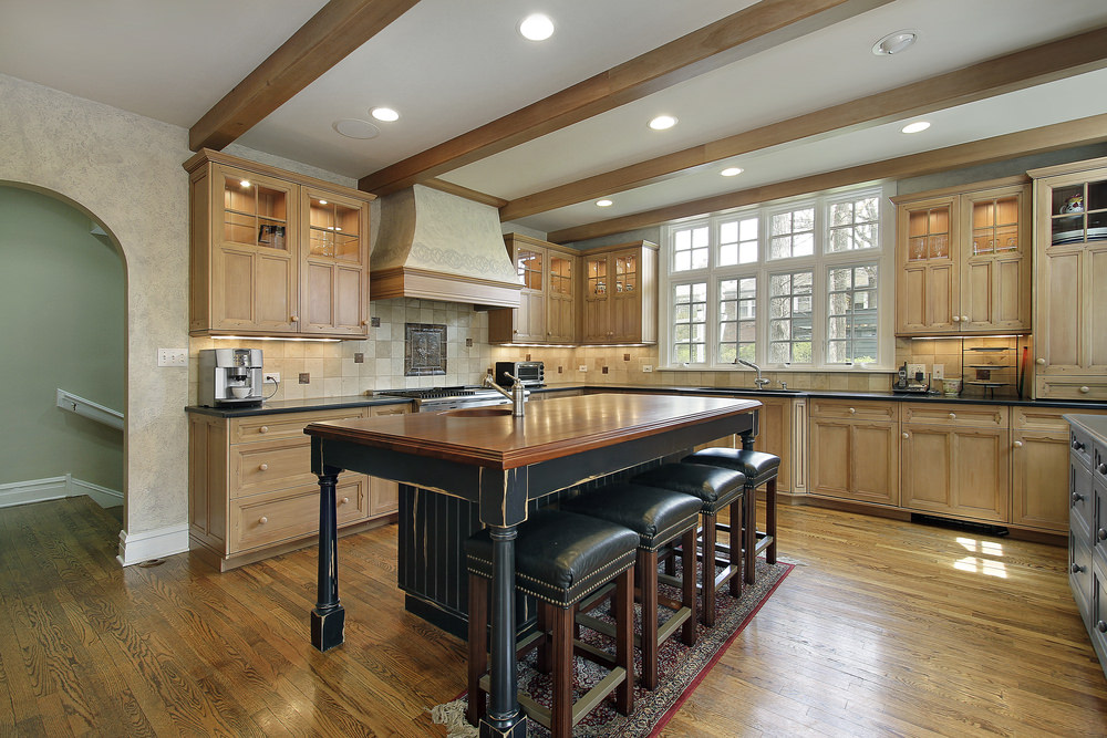 Spacious kitchen with hardwood floors and a ceiling with beams. It also features brown cabinetry and kitchen counters with black countertops, along with a center island that looks classy.