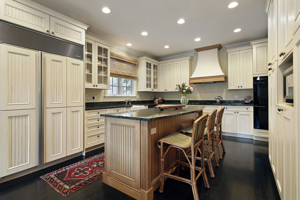 Medium-sized kitchen with black countertops on both kitchen counters and center island. The area is lighted by recessed lights.