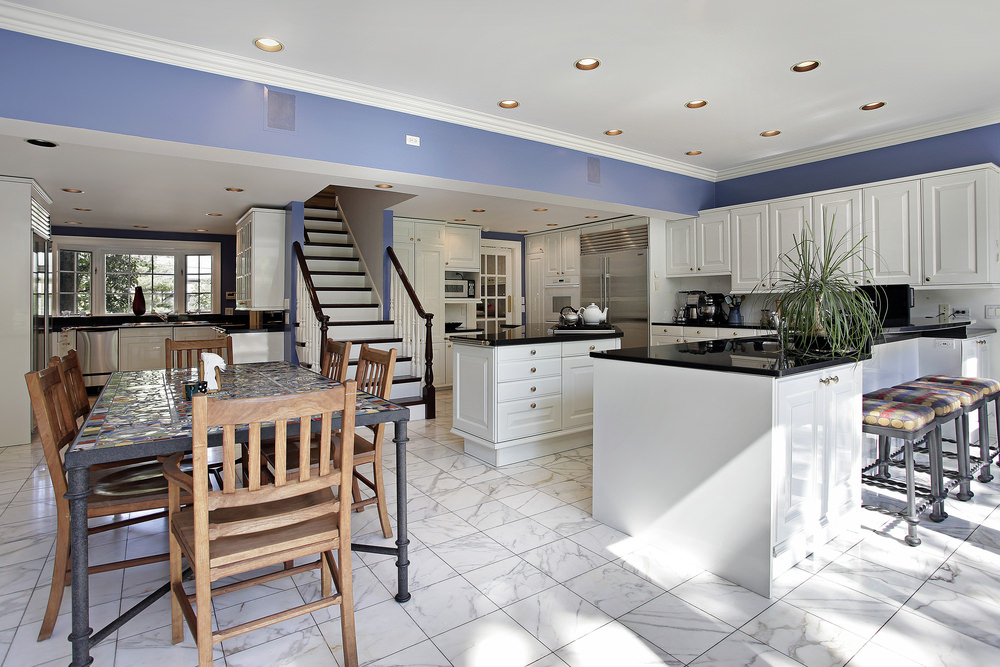 Large dine-in kitchen with marble tiles flooring and indigo blue walls. It has a dining table set for six and a breakfast bar counter featuring a black countertop.