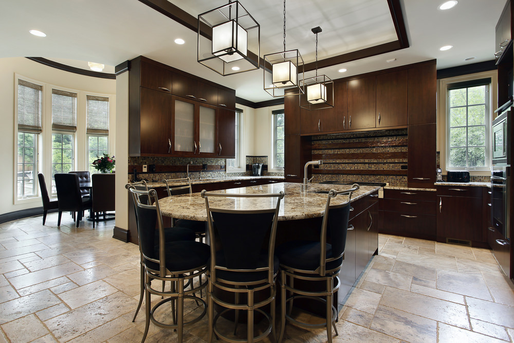 Large kitchen with tiles flooring and a gorgeous tray ceiling. It has brown kitchen counters and cabinetry, along with a large center island with a breakfast bar lighted by fancy pendant lights.