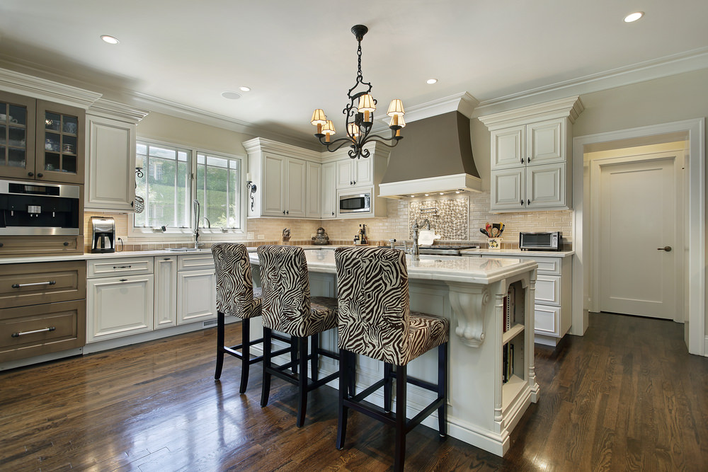 A spacious kitchen with hardwood floors and a regular ceiling. It offers a breakfast bar island with built-in shelving and is lighted by a gorgeous chandelier.