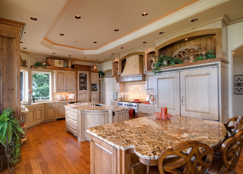 Large kitchen area with hardwood flooring and a beautiful tray ceiling. It offers a center island and a breakfast bar island, both having marble countertops.