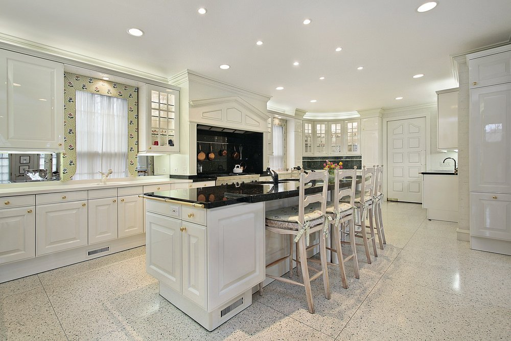 Large kitchen area with stylish tiles floors and a white ceiling with scattered recessed ceiling lights. The area also has a center island with a breakfast bar featuring a black countertop.