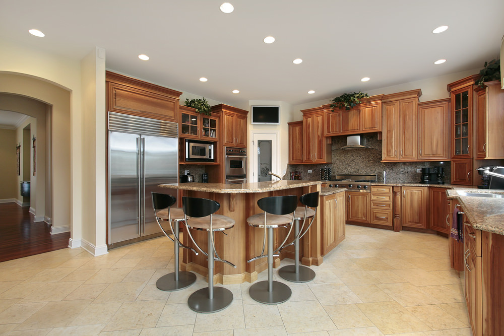 Spacious kitchen with tiles floors and a ceiling featuring recessed ceiling lights. It offers brown cabinetry and kitchen counters, along with a breakfast bar island.