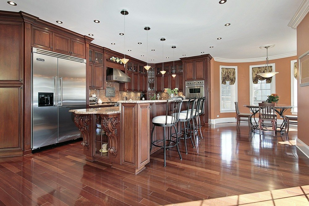 Dine-in kitchen boasting well-polished hardwood floors, brown cabinetry and kitchen counters, together with a breakfast bar and a round dining table set surrounded by brown walls.
