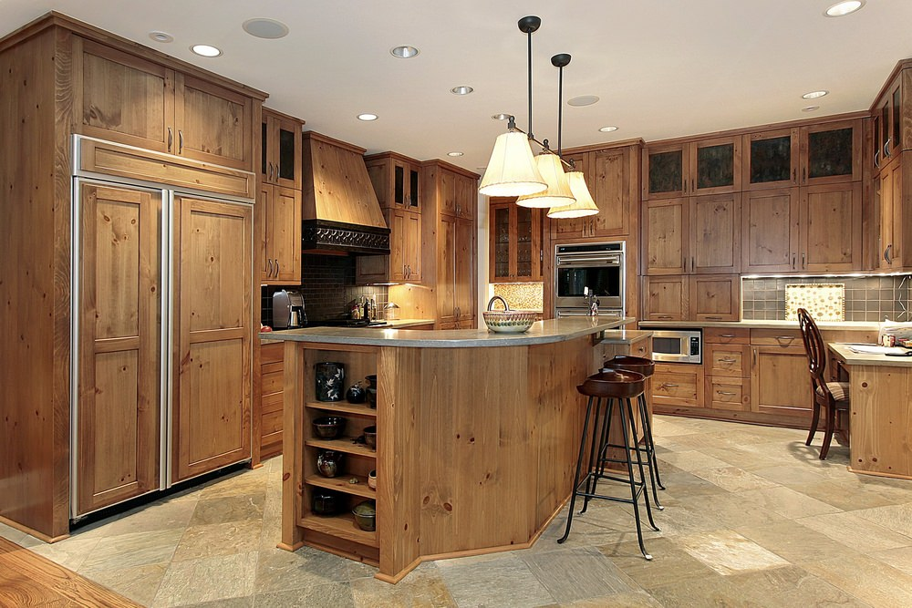 This kitchen features a built-in desk and a custom island with a breakfast bar, surrounded by brown kitchen counters and cabinetry.