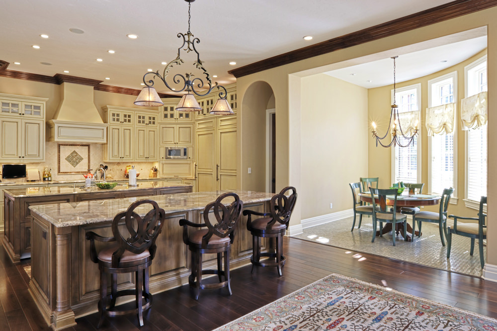 Large dine-in kitchen area with two islands, one serving as a breakfast bar lighted by classy ceiling lighting. There's a dining nook set by the window, lighted by a charming chandelier.