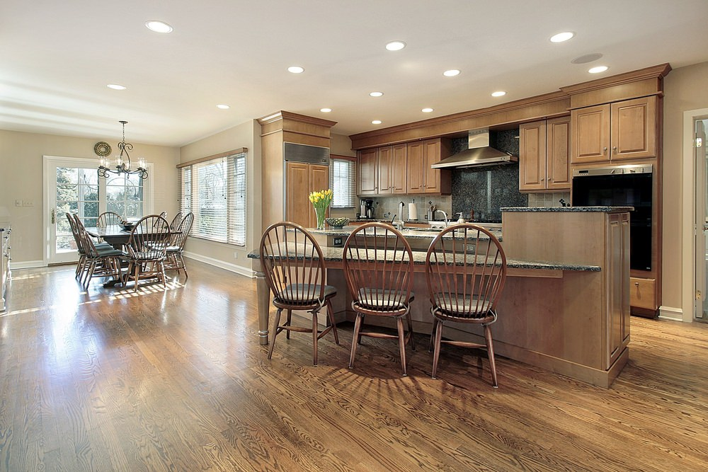 A spacious kitchen area with hardwood floors and a ceiling with recessed ceiling lights. It offers a stylish breakfast bar counter, along with a dining table set on the side.