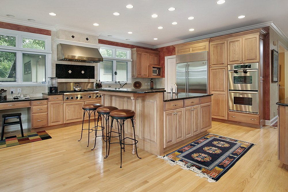 A spacious kitchen with brown kitchen counters and cabinetry, along with a center island with a breakfast bar counter. The kitchen also offers black countertops.