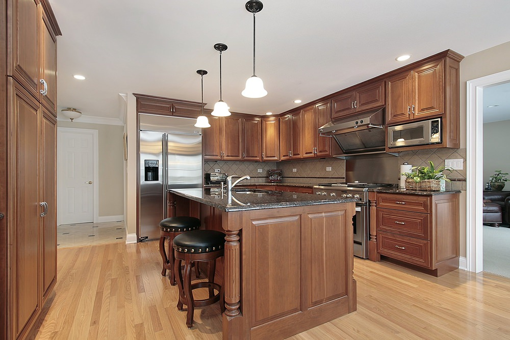 L-shaped kitchen featuring brown cabinetry and kitchen counters, along with a large center island. It also features black granite countertops, along with pendant and recessed ceiling lights.