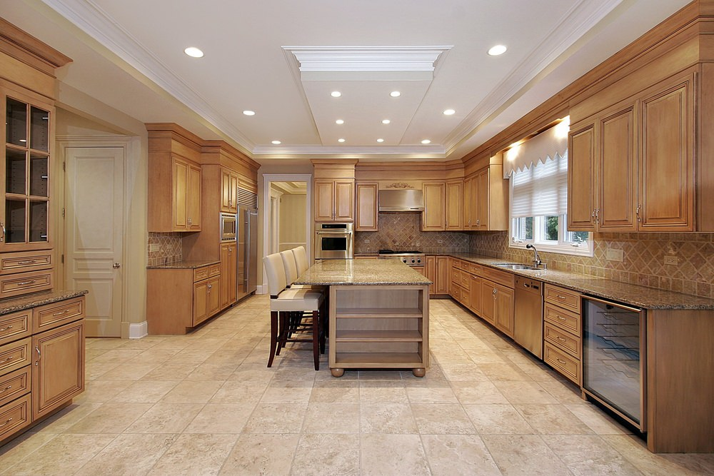 Large kitchen area with beige tiles floors and a beautiful white tray ceiling. It features brown cabinetry and kitchen counters, along with a center island featuring a breakfast bar and built-in shelving.