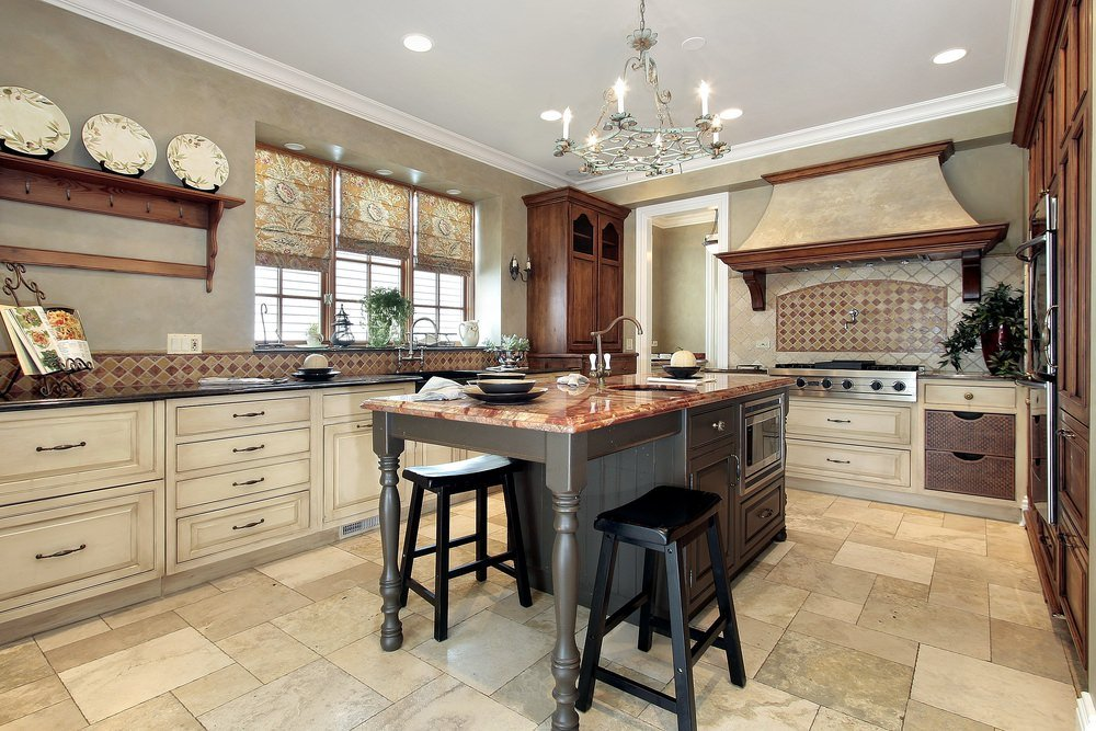 This kitchen offers a center island with a gorgeous countertop and has a breakfast bar lighted by classy ceiling light.