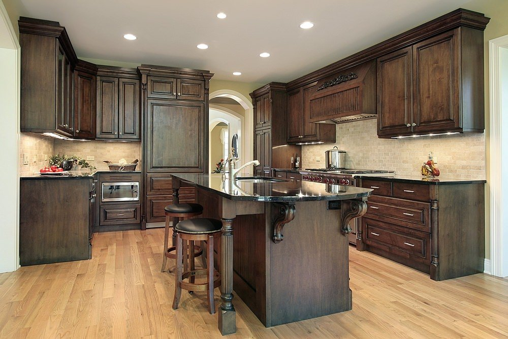 This kitchen features dark brown cabinetry and kitchen counters, along with a matching center island with a black countertop and has a breakfast bar.