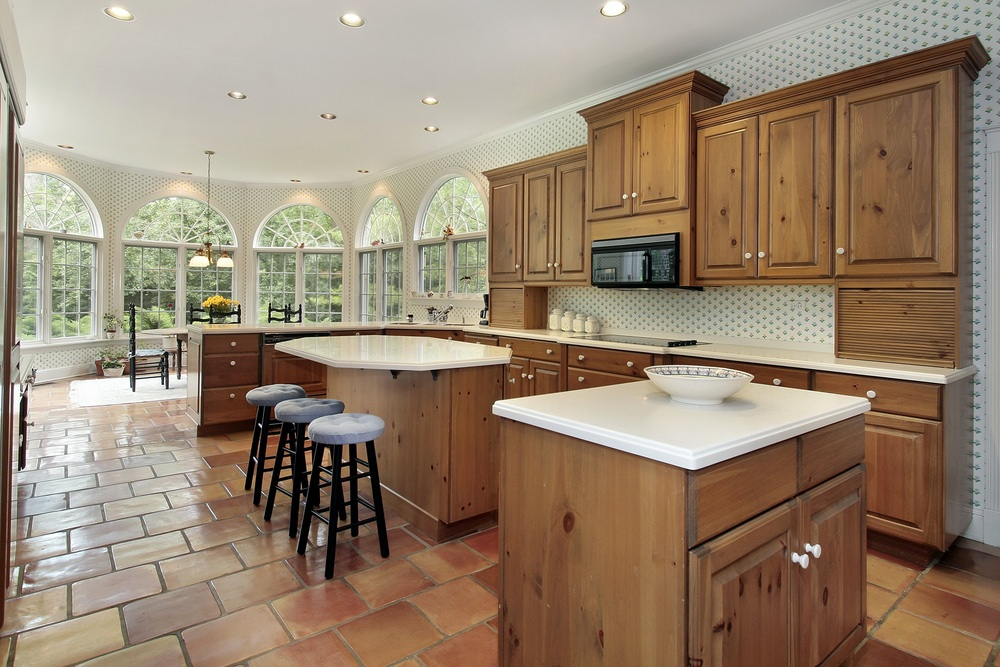 Large kitchen area with brown kitchen counters and cabinetry, along with two islands, one serving as a breakfast bar.
