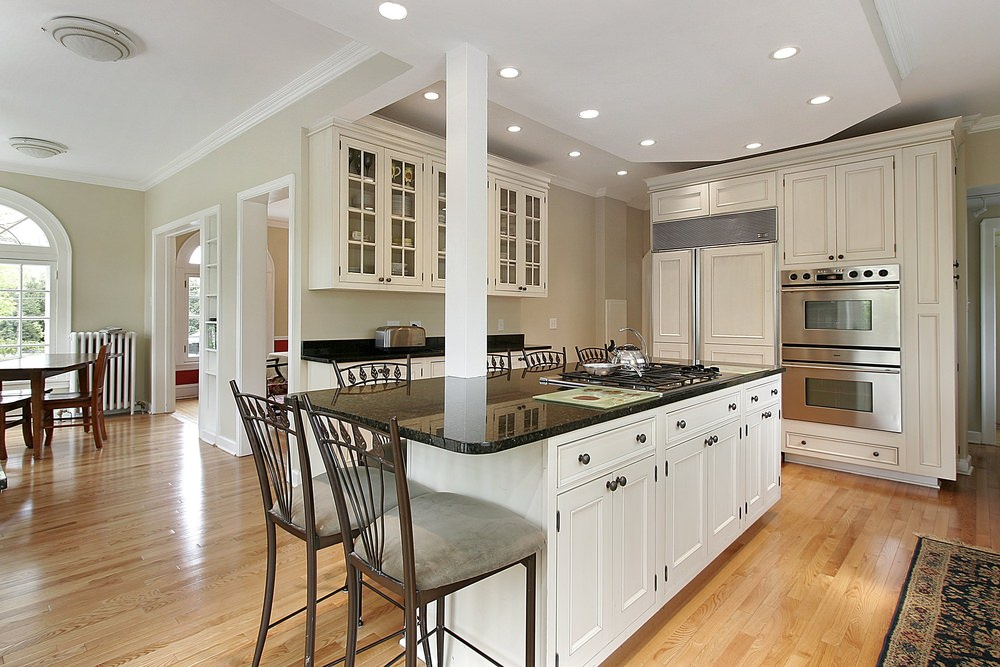 A kitchen with a tray ceiling and hardwood flooring. It has a large center island with a black countertop and has space for a breakfast bar.