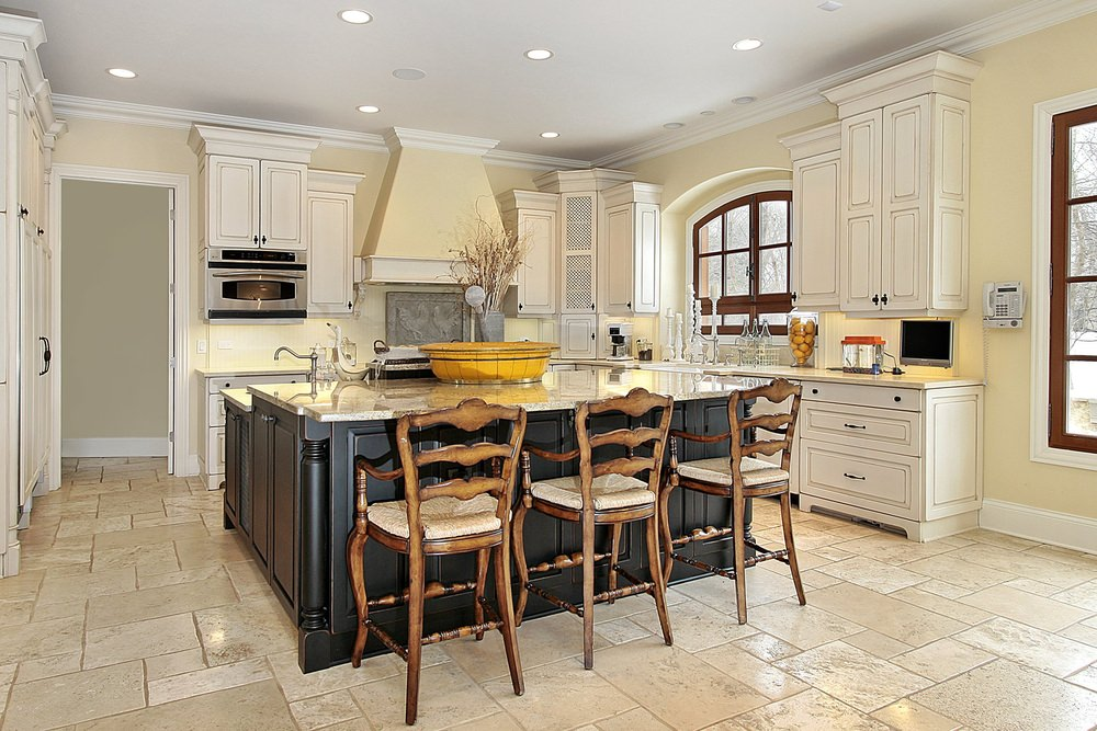 This kitchen features tiles flooring and light yellow walls. It offers a large center island with a breakfast bar counter, both featuring marble countertops.