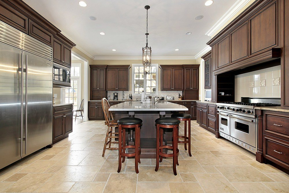 Large kitchen area with beige tiles floors and a regular white ceiling. It features brown cabinetry and kitchen counters, along with a center island featuring a breakfast bar.