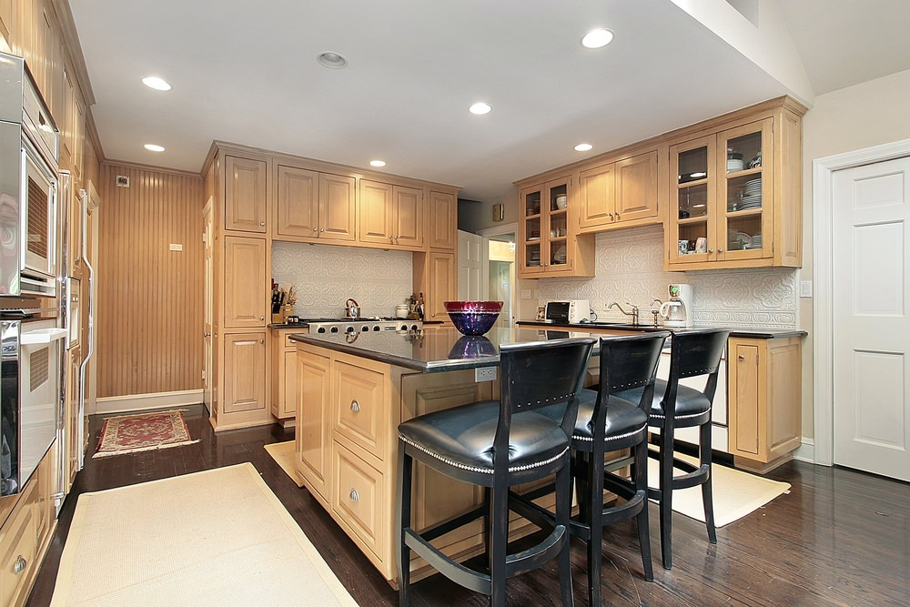 Kitchen with hardwood floors topped by area rugs. It offers a center island with a black countertop and has a breakfast bar.