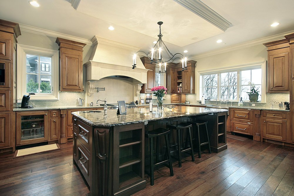 This kitchen boasts a massive center island with a stylish countertop and has space for a breakfast bar lighted by a gorgeous chandelier.