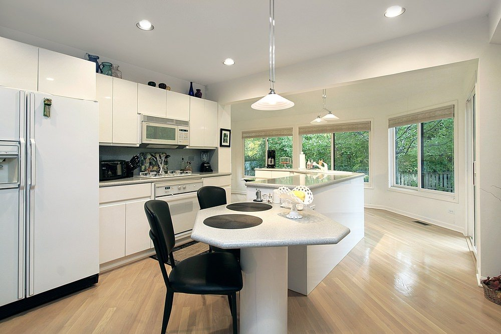 A close up look at this kitchen's custom breakfast bar counter beside the curved island with a beautiful countertop.