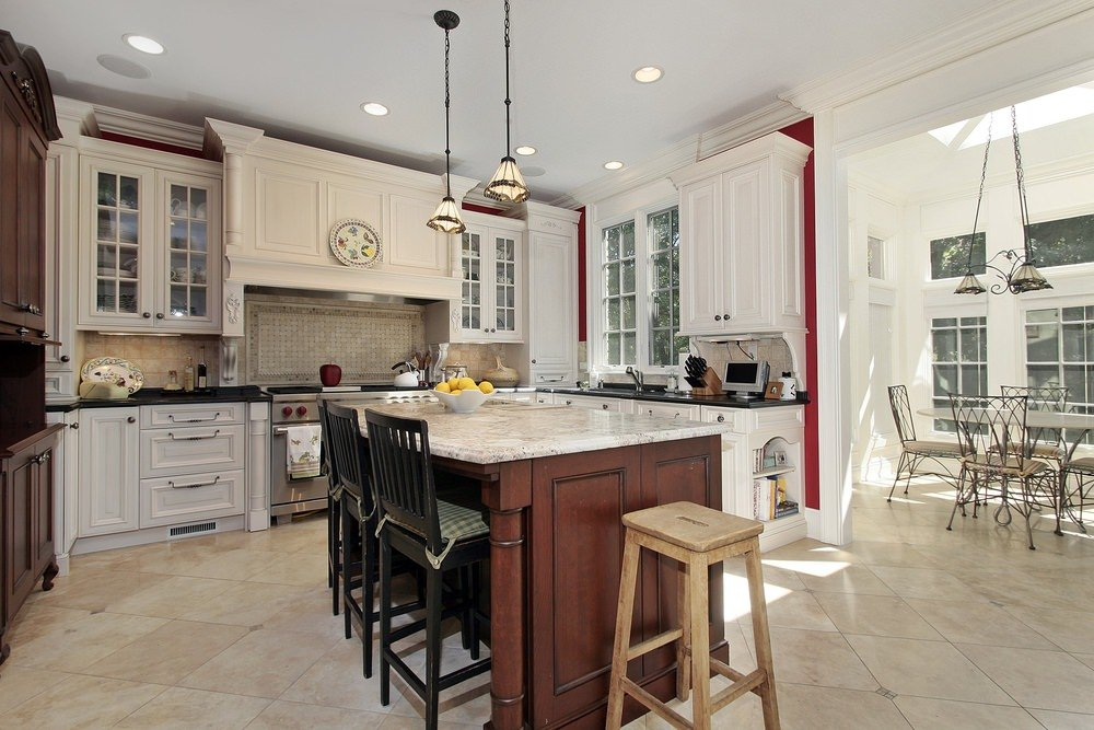 This kitchen features tiles flooring and a white ceiling. It offers a center island with a marble countertop lighted by pendant lights.