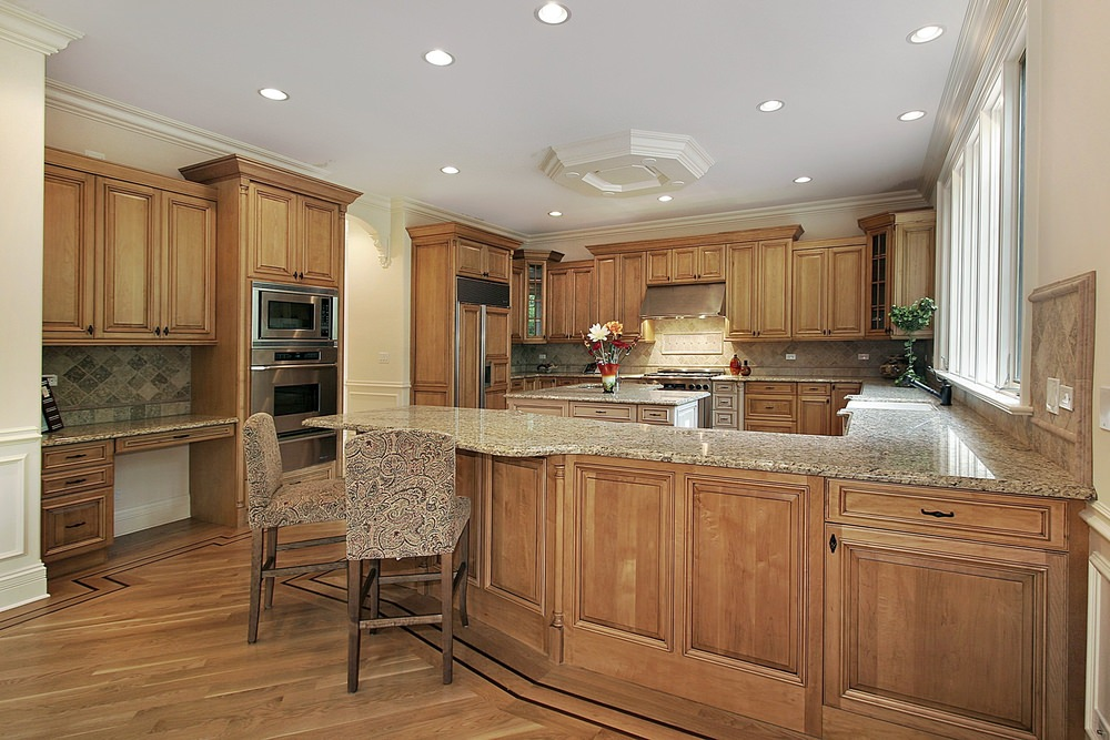 A galley-style kitchen with a breakfast bar counter and a built-in desk. The kitchen features granite countertops and has a square center island as well.