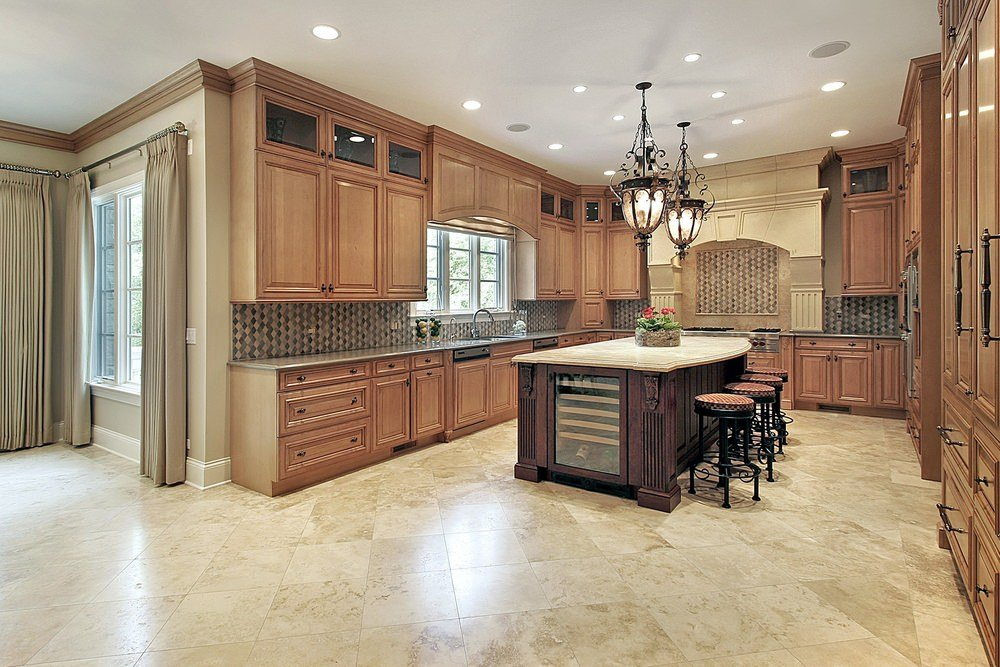 A spacious kitchen with tiles flooring and a white ceiling. It has brown kitchen counters and cabinetry, along with a large center island with a marble countertop lighted by gorgeous pendant lights.