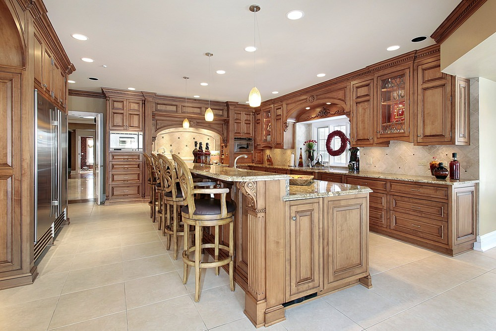 A kitchen featuring brown kitchen counters and cabinetry, together with a large island with a granite countertop and has a separate breakfast bar counter.