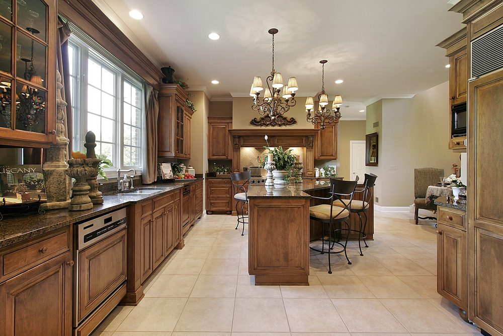 This kitchen has brown cabinetry and kitchen counters, along with a custom center island with a breakfast bar. The kitchen has granite countertops and chandelier lighting.