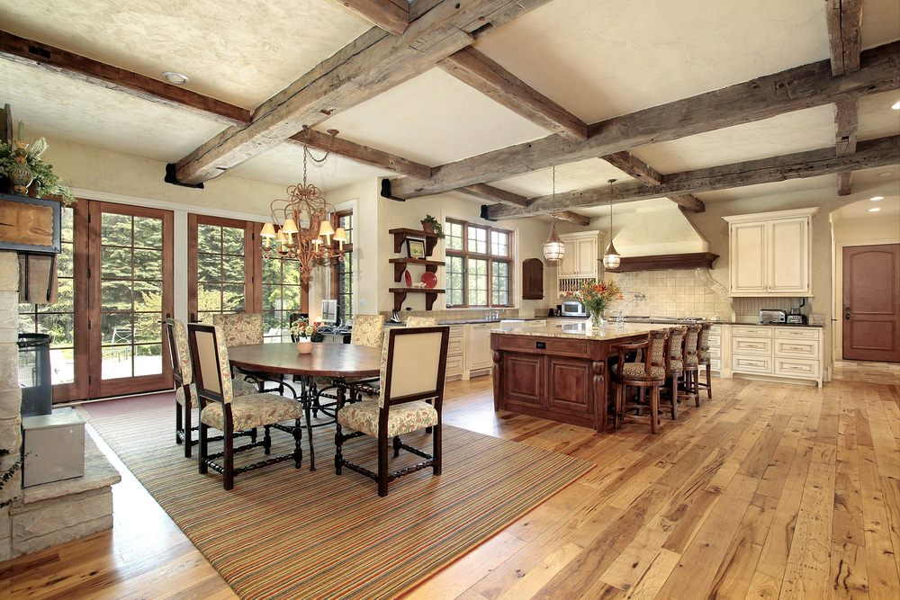 Large dine-in kitchen boasting an elegant oval-shaped dining table set and a kitchen with a breakfast bar island set under the home's ceiling with large rustic beams.