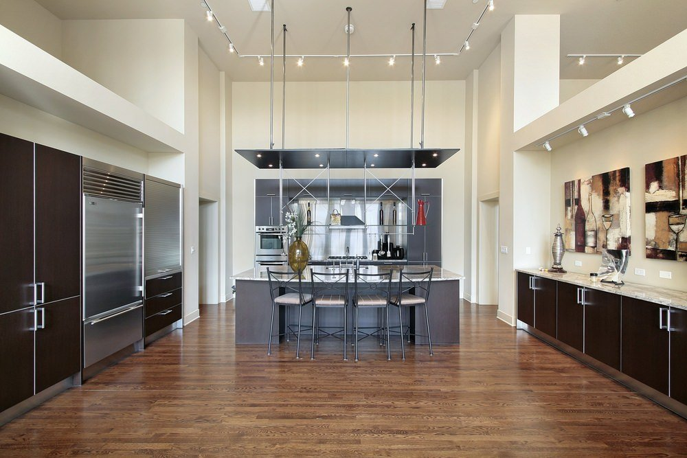 This kitchen features hardwood floors and a tall ceiling with scattered ceiling lights, It offers a large center island with a breakfast bar.
