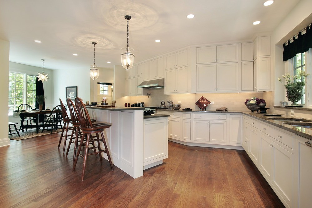 A spacious kitchen featuring hardwood flooring and a white ceiling. It offers an island with a breakfast bar counter along with a dining nook on the side.