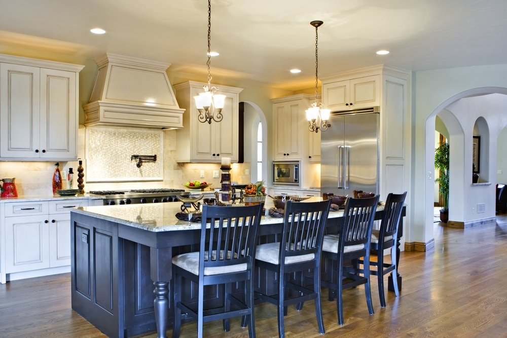 Spacious kitchen area with a navy blue island with a marble countertop and has space for a breakfast bar lighted by pendant lights.