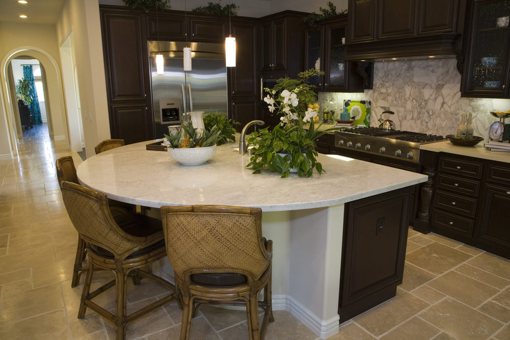 A focused look at this kitchen's gorgeous custom made island with a breakfast bar and has a classy countertop.