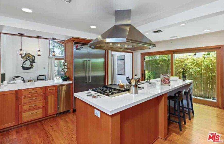 This kitchen offers a brown center island with a white countertop featuring space for a breakfast bar.