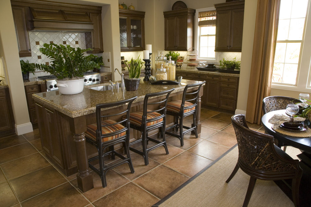 A dine-in kitchen featuring a round dining nook on the side and a breakfast bar island with a granite countertop.