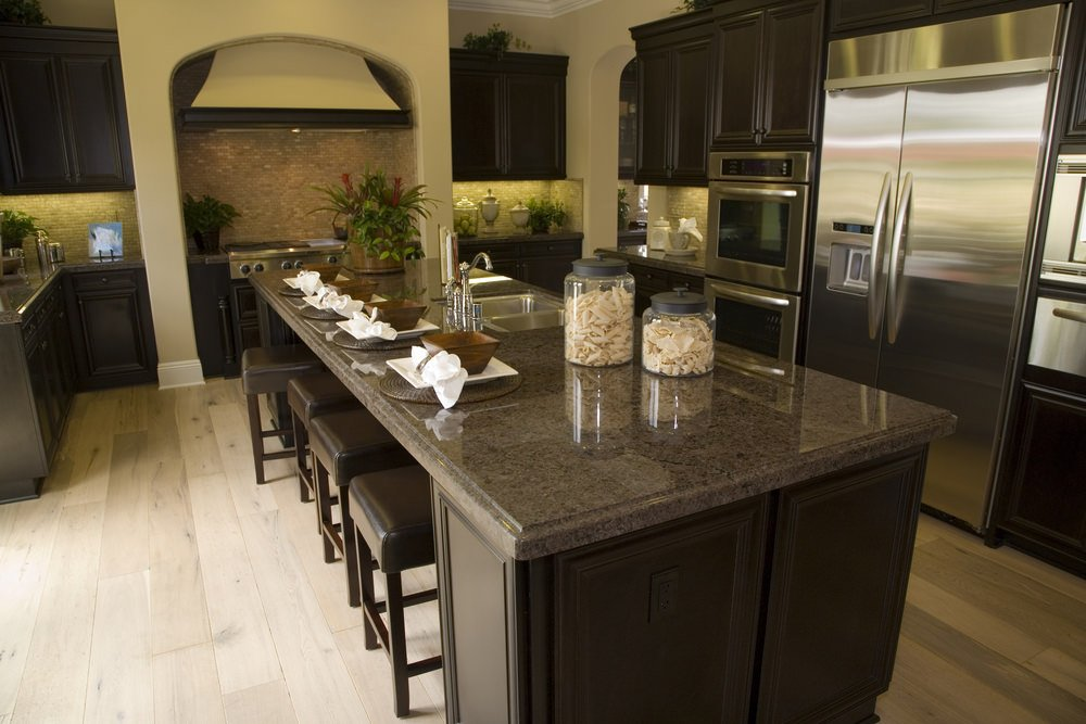 A focused look at this kitchen's island with a black granite countertop and has space for a breakfast bar.