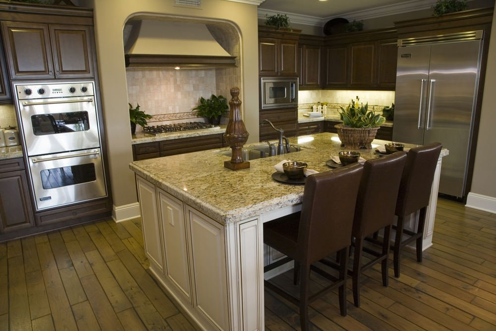 This kitchen features hardwood floors and brown cabinetry and kitchen counters. It has a center island with a granite countertop as well.