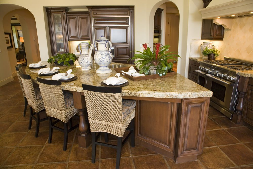 This kitchen boasts a large custom center island with a marble countertop and has a breakfast bar. The area has stylish brown tiles flooring.