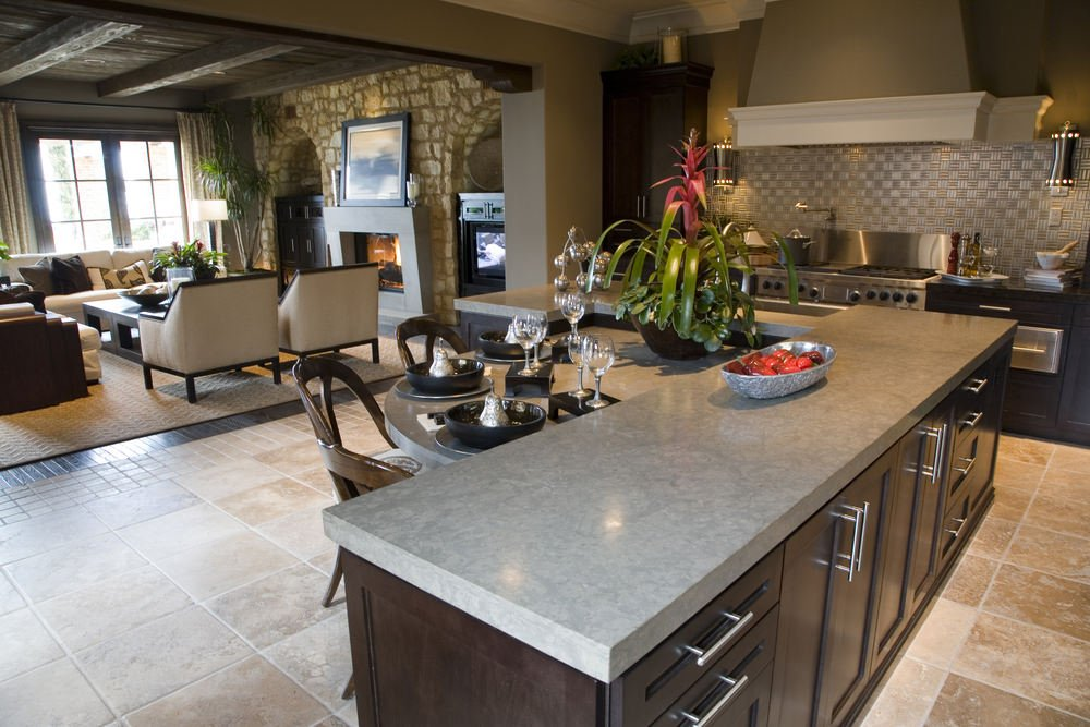 Modern L-shaped kitchen featuring an L-shaped island with a breakfast bar counter. The area features tiles flooring and gray walls.