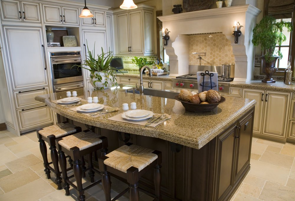 A focused look at this kitchen's island with a granite countertop and has a breakfast bar. The area features tiles flooring and pendant lights.